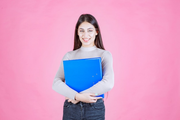 Mädchen, das einen blauen projektordner hält und erfolgreich und glücklich aussieht