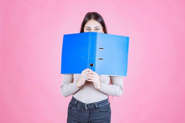 Mädchen, das einen blauen projektordner hält und ihr gesicht dahinter versteckt
