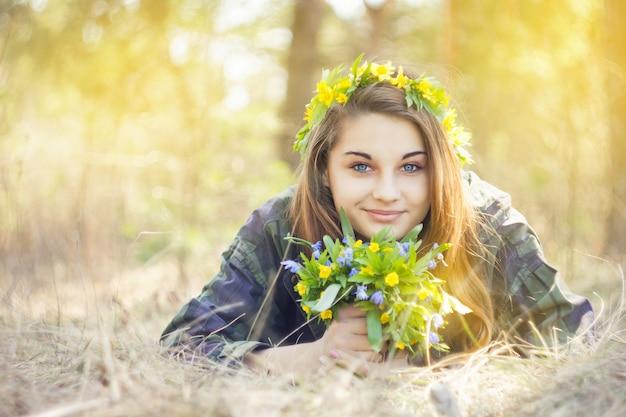 Mädchen, das einen blumenstrauß von frühlingsblumen hält