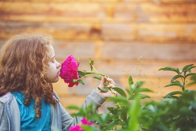 Mädchen, das einen blumenstrauß von gänseblümchen, foto im profil riecht.
