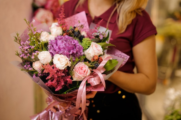 Mädchen, das einen blumenstrauß von rosen, astilba und beeren hält