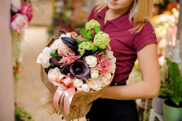 Mädchen, das einen blumenstrauß von rosen, callas, orchidee und hortensie hält