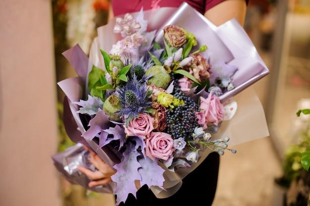 Mädchen, das einen blumenstrauß von rosen, getrockneten mohnblumen und lila blättern hält