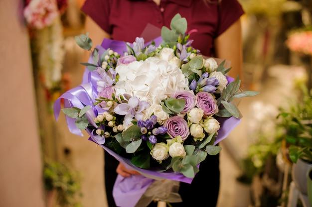 Mädchen, das einen blumenstrauß von rosen, hortensie, orchidee, eustoma, pfingstrosen hält
