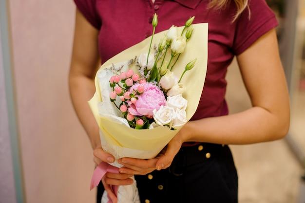 Mädchen, das einen blumenstrauß von rosen und pfingstrose hält