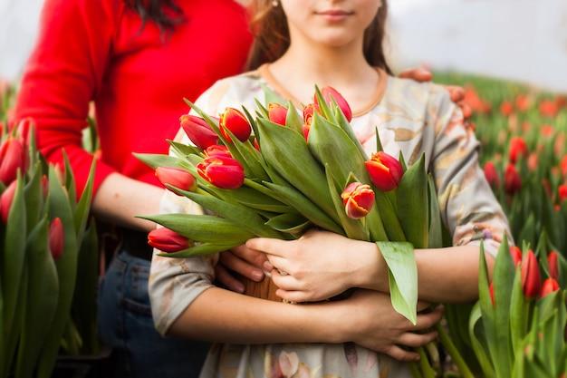 Mädchen, das einen blumenstrauß von tulpen hält, gewachsen in einem gewächshaus