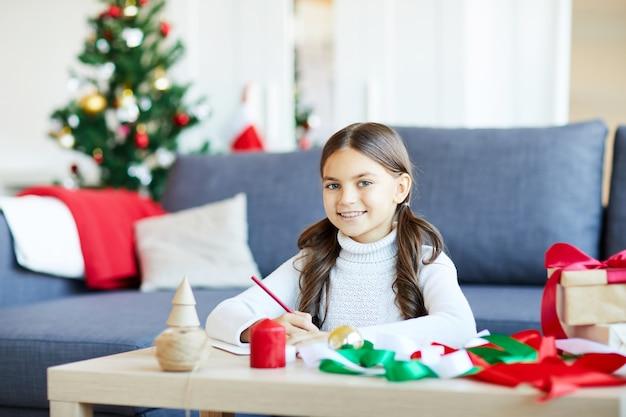 Mädchen, das einen brief für santa schreibt