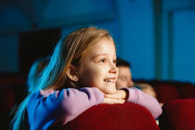 Mädchen, das einen film an einem kino sieht