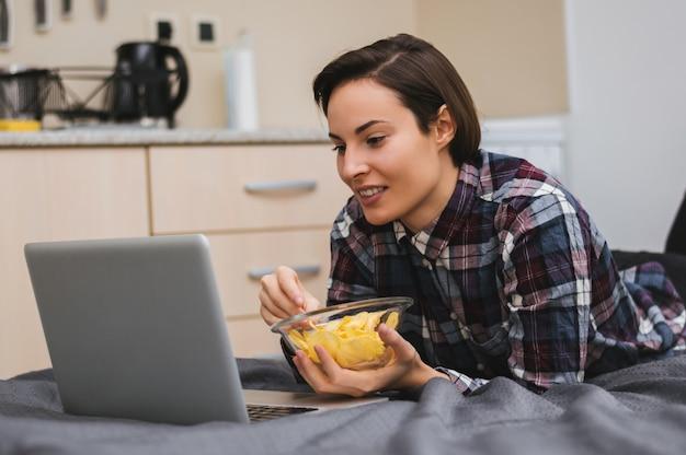 Mädchen, das einen film auf computer aufpasst und auf das bett legt und chips isst