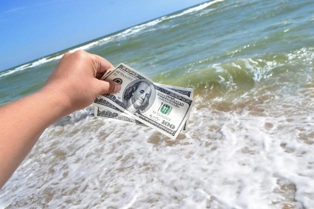 Mädchen, das einen geldschein von 300 dollar auf dem hintergrund der meereswellen hält