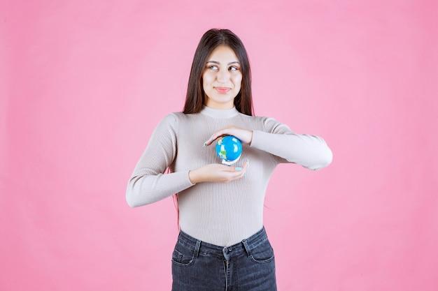 Mädchen, das einen globus zwischen den händen hält