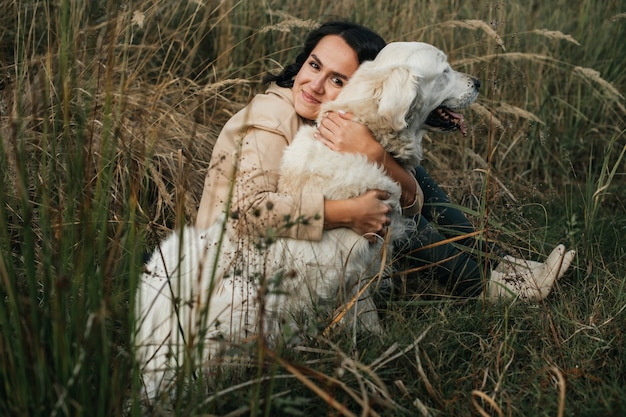 Mädchen, das einen golden retriever-hund auf dem feld umarmt