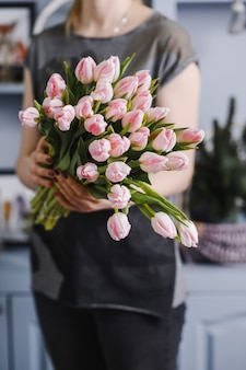 Mädchen, das einen großen strauß tulpen in ihren händen hält.