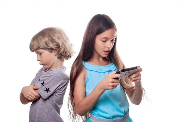Mädchen, das einen handy und einen blonden jungen zurück stehen mit einem ausdrucksvollen beleidigten gesicht betrachtet