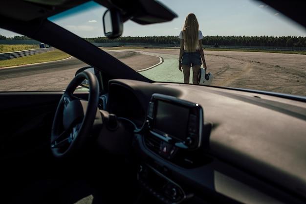 Mädchen, das einen helm neben einem sportwagen hält