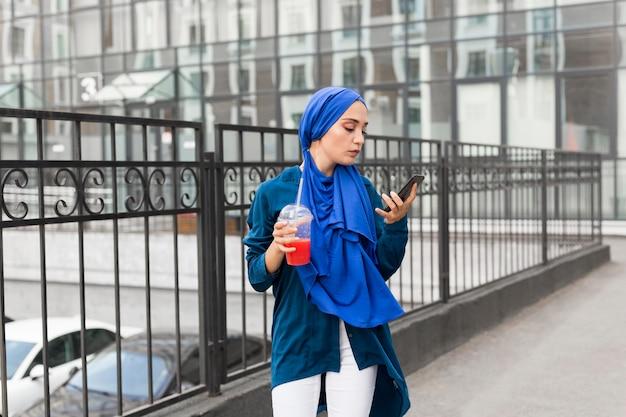 Mädchen, das einen hijab trägt und einen smoothie hält, während sie ihr telefon betrachtet