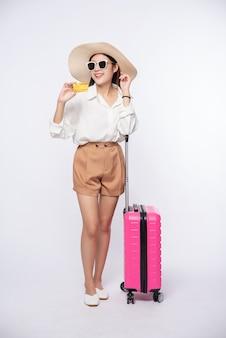 Mädchen, das einen hut hält, der kreditkarte und koffer hält, um zu reisen