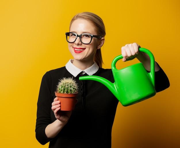 Mädchen, das einen kaktus wässert