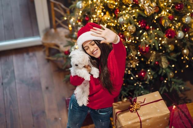 Mädchen, das einen kleinen hund in ihren armen am silvesterabend hält