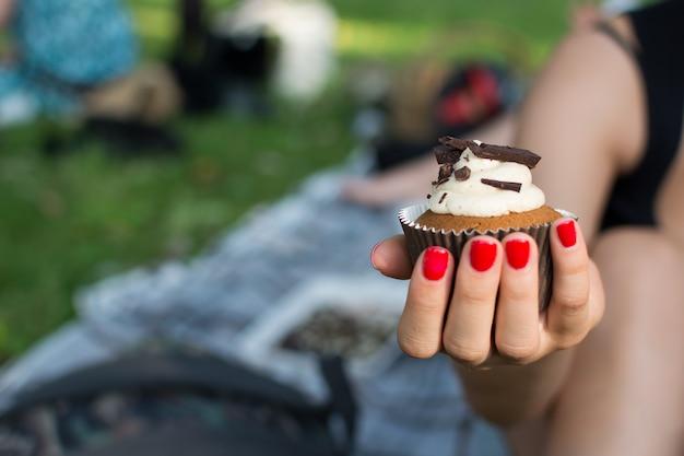Mädchen, das einen kleinen kuchen beim haben des picknicks hält