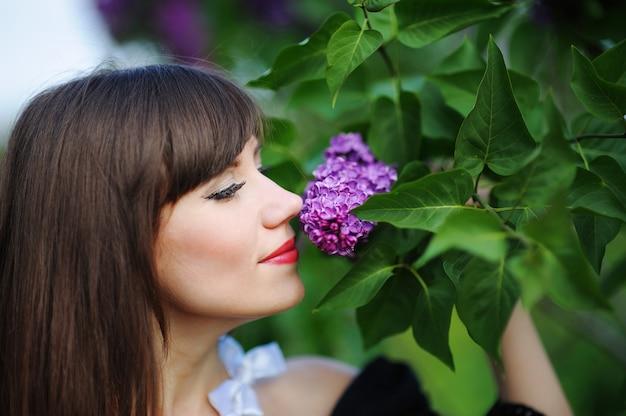 Mädchen, das einen lila flieder im frühling im park riecht