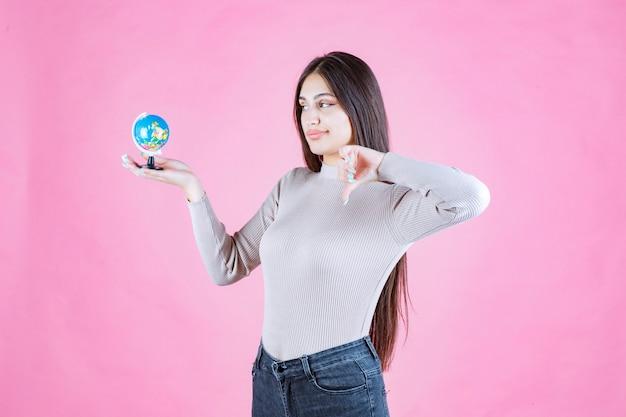 Mädchen, das einen mini-globus hält und daumen nach unten macht