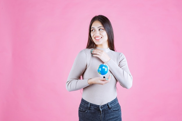 Mädchen, das einen mini-globus hält und lächelt