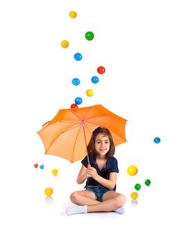 Mädchen, das einen regenschirm beim regnen der farbigen bälle hält