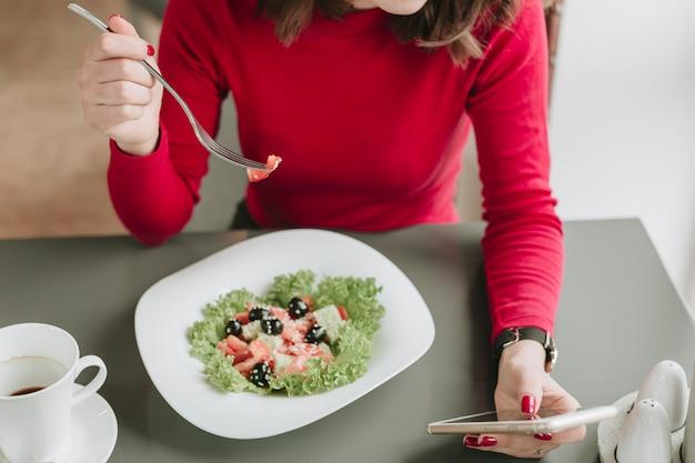 Mädchen, das einen salat in einem restaurant isst