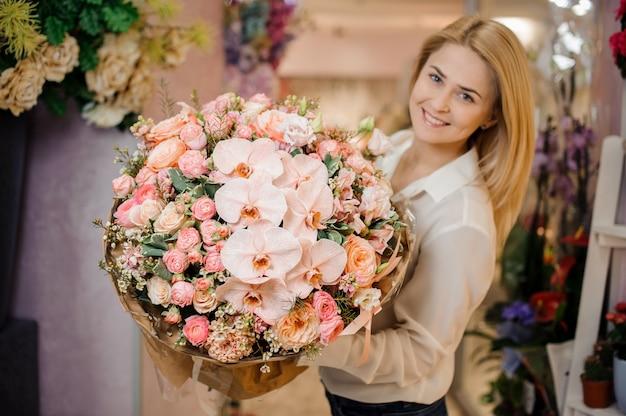 Mädchen, das einen schönen strauß orchidee und rosen hält