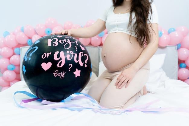 Mädchen, das einen schwarzen ballon mit einem jungen oder einem mädchen auf einer gender-enthüllungsparty hält