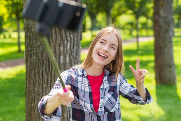 Mädchen, das einen selfie stock für ein foto verwendet