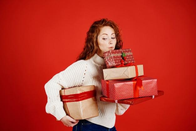 Mädchen, das einen stapel weihnachtsgeschenke trägt