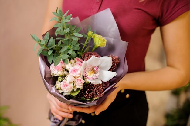 Mädchen, das einen stilvollen blumenstrauß von rosen, orchidee, eukalyptus hält