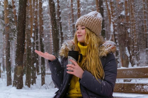 Mädchen, das einen thermobecher hält und schneeflocken fängt, während es auf einer bank im winterpark sitzt
