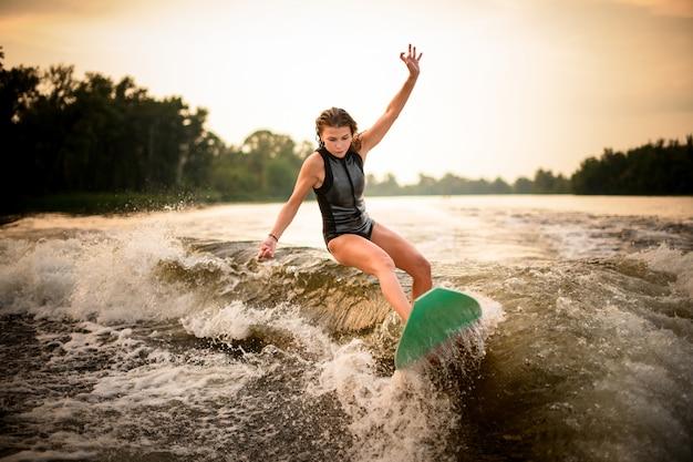 Mädchen, das einen trick auf dem grünen wakeboard auf dem fluss im sonnenuntergang macht