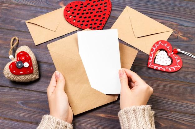 Mädchen, das einen umschlag mit valentinsgrußherzen hält. valentinstagkonzept mit copyspace