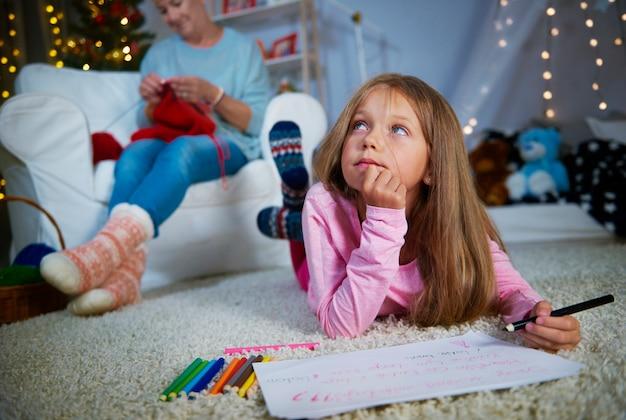 Mädchen, das einen weihnachtsbrief zum weihnachtsmann schreibt
