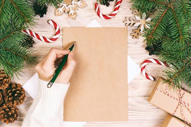 Mädchen, das einen weihnachtsbuchstabenhintergrund schreibt