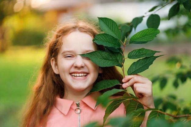 Mädchen, das einen zweig mit grünen blättern nahe ihrem gesicht hält
