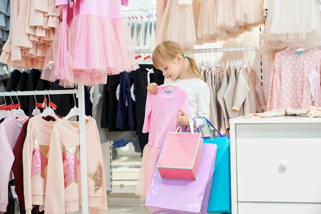 Mädchen, das einkaufstaschen hält und rosa kleid wählt.