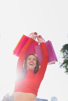 Mädchen, das einkaufstaschen über ihrem kopf hält