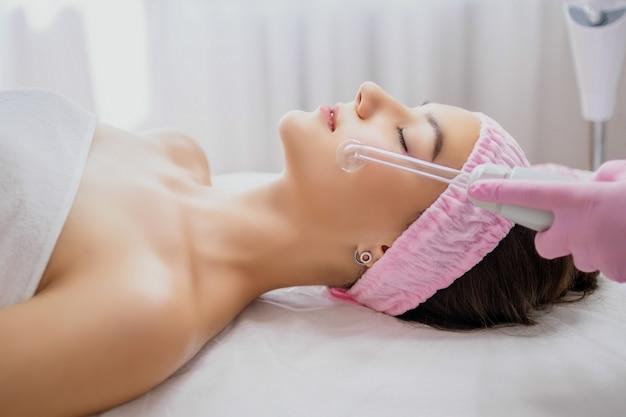 Mädchen, das elektrische massage des darsonval-verfahrens am schönheitssalon erhält