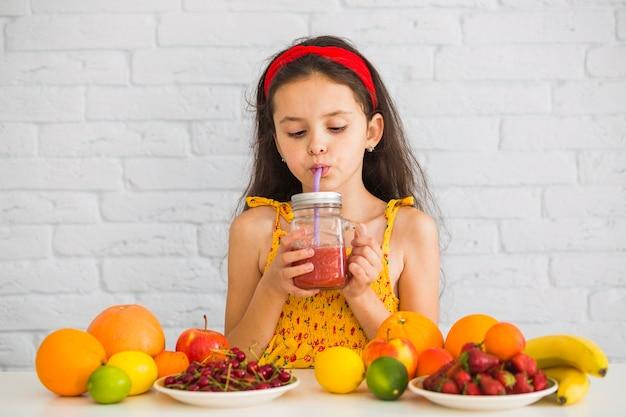 Mädchen, das erdbeeresmoothies mit bunten früchten trinkt