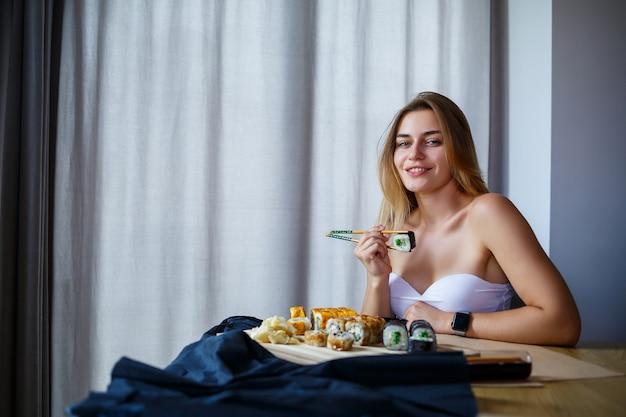 Mädchen, das essstäbchen-sushi-rolle hält. junge frau, die köstliches frisches japanisches sushi isst.