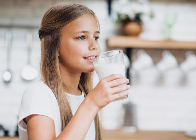 Mädchen, das fertig wird, etwas milch zu trinken