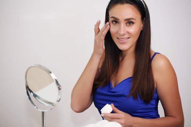 Mädchen, das feuchtigkeitscreme auf gesicht anwendet. hautpflege- und schönheitskonzept.