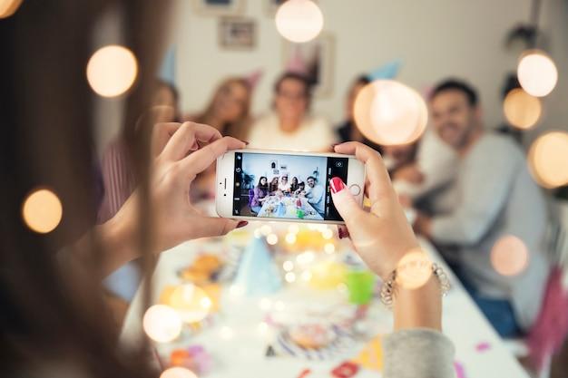 Mädchen, das foto des geburtstages mit smartphone macht