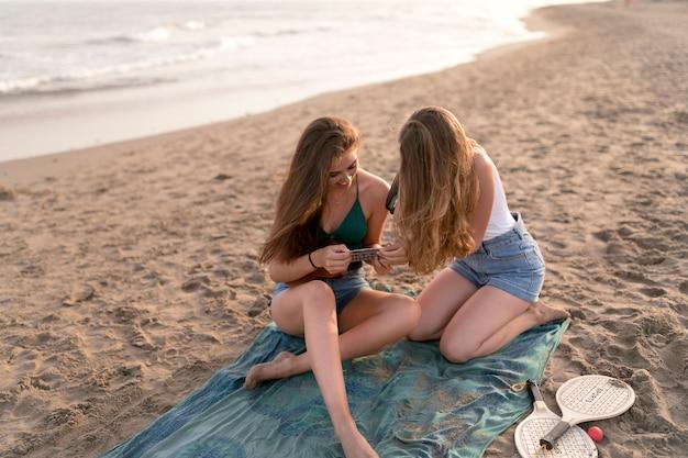 Mädchen, das foto ihres freundes spielt ukulele durch sofortige kamera am strand macht