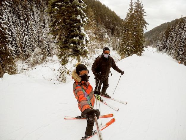 Mädchen, das foto mit einem selfie-stock beim skifahren mit einem jungen mann in einem wald nimmt.